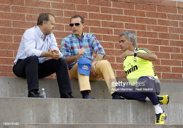 Head coach Jose Mourinho of Real Madrid chats with Real Madrid's formers players Emilio Butragueno and Miguel Pardeza during a training session at...
