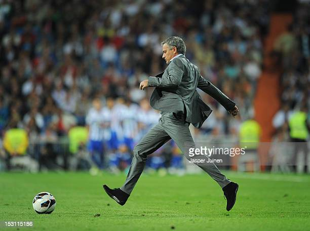 Head coach Jose Mourinho of Real Madrid kicks the ball on the pitch back to his players to resume the game after conceding an early opening goal...