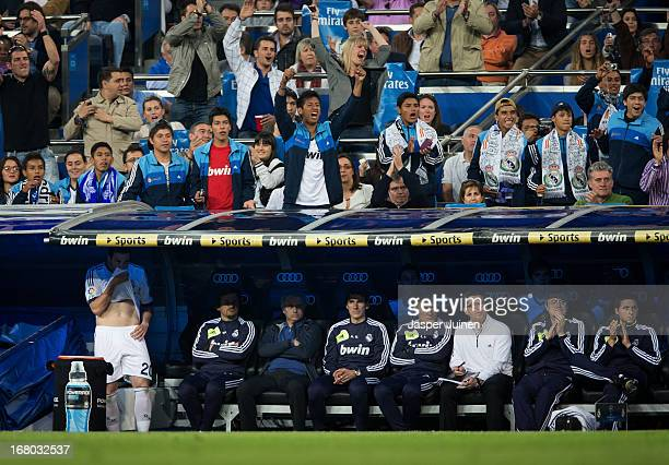 Head coach Jose Mourinho of Real Madrid sits quiet with his technical staff while the public above them celebrate a goal by Cristiano Ronaldo during...