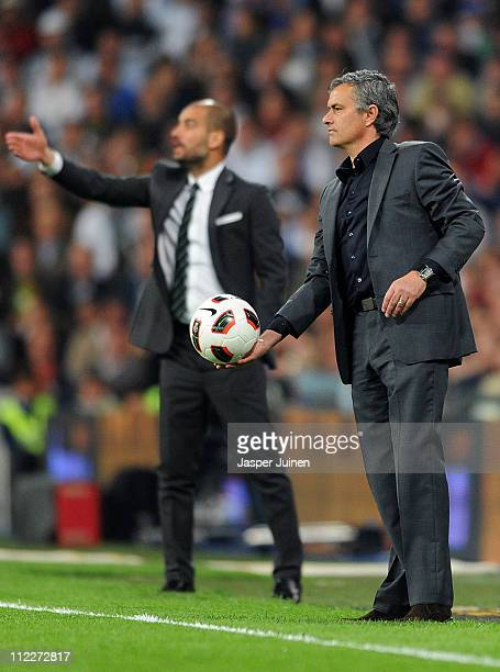 Head coach Jose Mourinho of Real Madrid throws the ball backdropped by head coach Josep Guardiola of Barcelona during the la Liga match between Real...