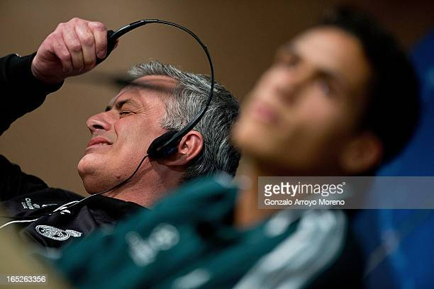 Head coach Jose Mourinho takes off his headphones annoyed while Real Madrid player Raphael Varane listen to questions from the media during a press...
