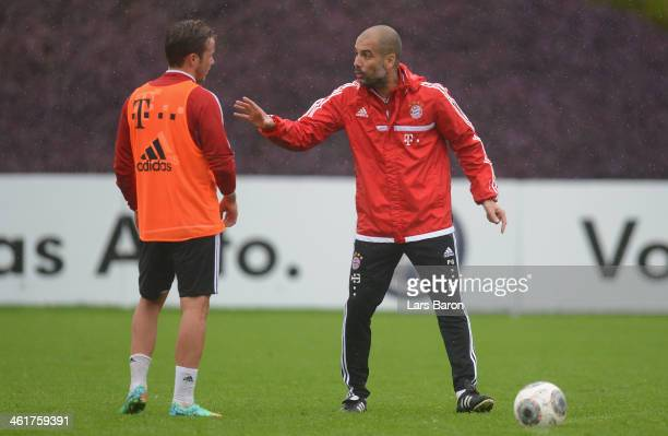Head coach Josep Guardiola gives instructions to Mario Goetze during a training session at day 7 of the Bayern Muenchen training camp at ASPIRE...