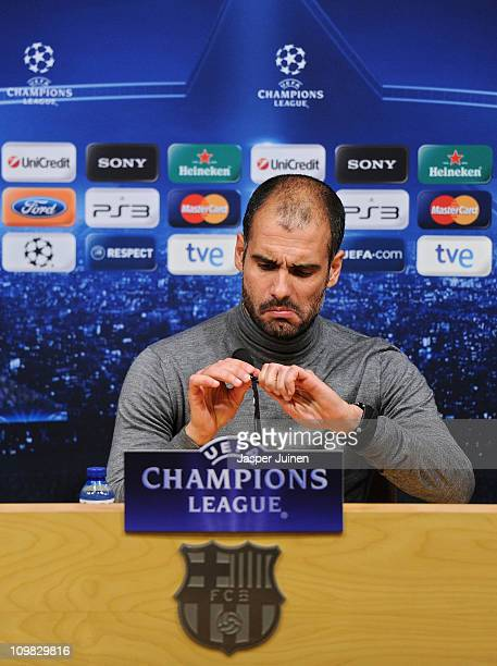 Head coach Josep Guardiola of Barcelona fiddles with a microphone during a press conference ahead of their UEFA Champions League round of 16 second...