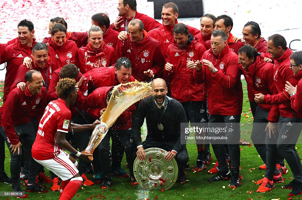 Head coach Josep Guardiola (C) of Bayern Muenchen is poured beer by David Alaba while celebrating Bundesliga champions with staffs after the Bundesliga match between FC Bayern Muenchen and Hannover 96 at Allianz Arena on May 14, 2016 in Munich, Germany.