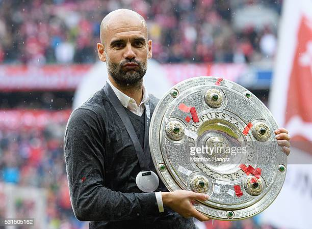 Head coach Josep Guardiola of Bayern Muenchen poses with the Meisterschale as he celebrates the Bundesliga champions after the Bundesliga match...