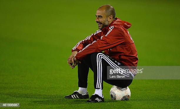 Head coach Josep Guardiola reacts while sitting on a ball during a training session at day 8 of the Bayern Muenchen training camp at ASPIRE Academy...