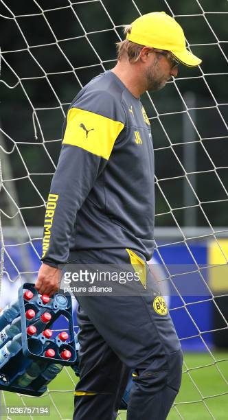 Head coach Juergen Klopp of Borussia Dortmundin carries a case of water bottles during a training session at the team's training camp in Bad Ragaz,...