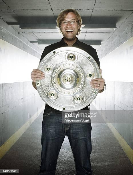 Head coach Juergen Klopp of German Bundesliga football club Borussia Dortmund poses with the German Championships Bundesliga throphy during a...