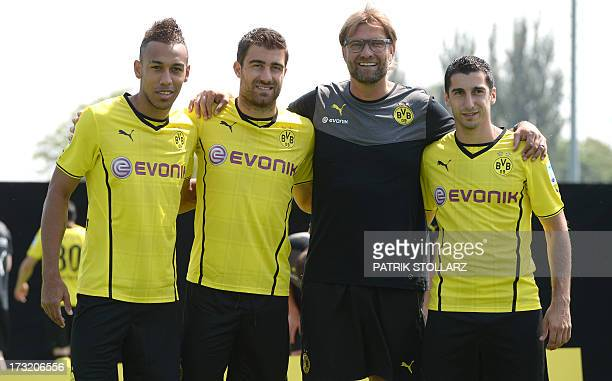 Head coach Juergen Klopp poses with new players PierreEmerick Aubameyang Sokratis and Henrikh Mkhitaryan during a team photo call of German first...