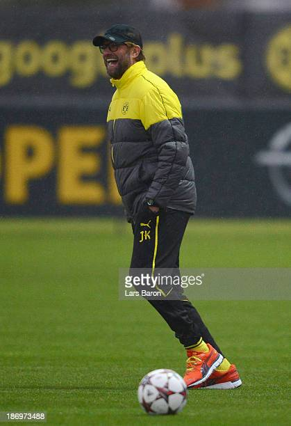HEad coach Juergen Klopp smiles during a Borussia Dortmund training session ahead of the UEFA Champions League Group F match against Arsenal on...