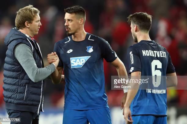 Head coach Julian Nagelsmann of Hoffenheim celebrates with Sandro Wagner and Havard Nordtveit after the Bundesliga match between 1 FSV Mainz 05 and...