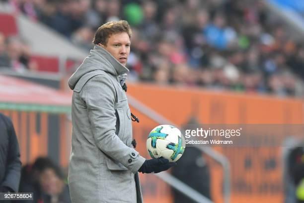 Head coach Julian Nagelsmann of Hoffenheim holds a ball in his right hand during the Bundesliga match between FC Augsburg and TSG 1899 Hoffenheim at...