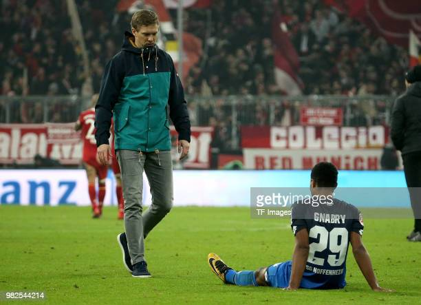 Head coach Julian Nagelsmann of Hoffenheim walks and Serge Gnabry of Hoffenheim on the ground during the Bundesliga match between FC Bayern Muenchen...