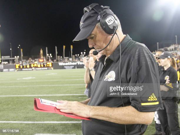 Head coach June Jones of the Hamilton TigerCats checks plays during a preseason game against the Toronto Argonauts at Tim Hortons Field on June 1...