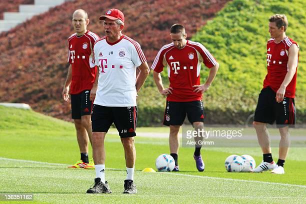 Head coach Jupp Heynckes walks past Arjen Robben Franck Ribery and Bastian Schweinsteiger during a training session of Bayern Muenchen at the ASPIRE...