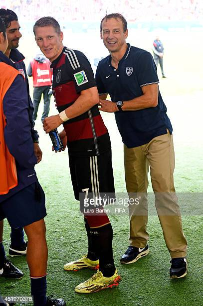 Head coach Jurgen Klinsmann of the United States talks to Bastian Schweinsteiger of Germany as he walks off in the tunnel after the 2014 FIFA World...