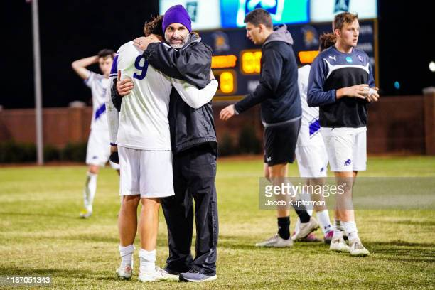 Head coach Justin Serpone of Amherst Mammoths comforts German Giammattei of Amherst Mammoths after their loss during the Division III Men's Soccer...