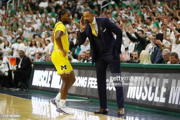 Head coach Juwan Howard of the Michigan Wolverines talks with Zavier Simpson during the second half while playing the Michigan State Spartans at the...