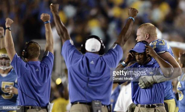 Head Coach Karl Dorrell of the UCLA Bruins is hugged by Ed Blanton as time expires during his teams' 2117 win over the Washington Huskies in their...