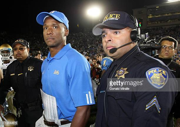 Head Coach Karl Dorrell of the UCLA Bruins walks off the field with security after his team's 206 upset loss to the Notre Dame Fighting Irish during...