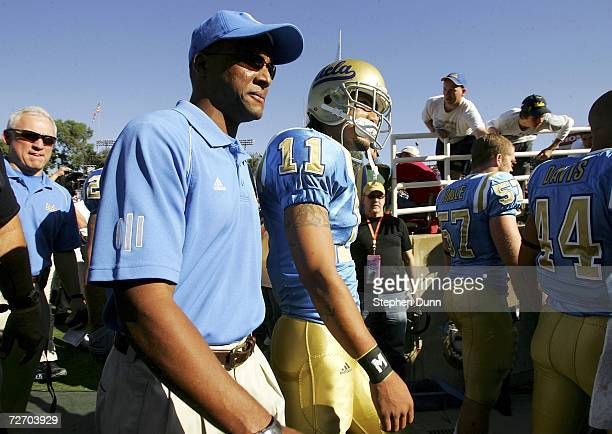 UCLA head coach Karl Dorrell walks onto field with Dennis Keyes of the UCLA Bruins prior to the start of the game against the USC Trojans on December...