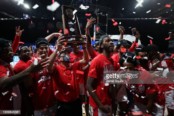 Head coach Kelvin Sampson of the Houston Cougars hoists the trophy after defeating the Oregon State Beavers in the Elite Eight round of the 2021 NCAA...