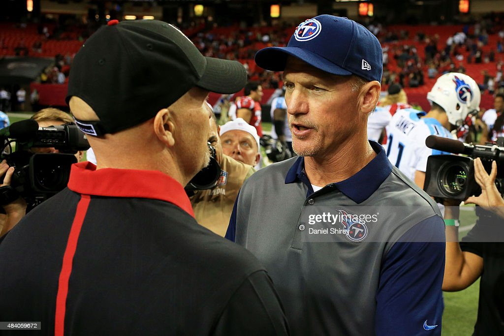 Head coach Ken Whisenhunt of the Tennessee Titans (R) meets with head coach Dan Quinn of the Atlanta Falcons after the preseason game at the Georgia Dome on August 14, 2015 in Atlanta, Georgia.