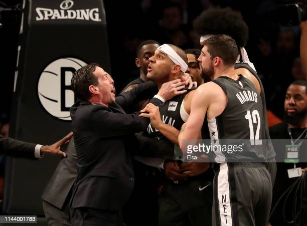Head coach Kenny Atkinson and Joe Harris of the Brooklyn Nets hold back Jared Dudley at Barclays Center after a foul by Joel Embiid of the...