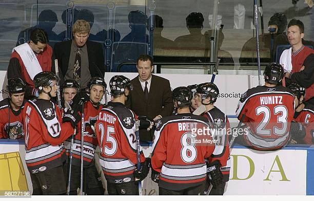 Head coach Kevin Dineen of the Portland Pirates talks to players at the bench during a break in the game against the Bridgeport Sound Tigers at the...