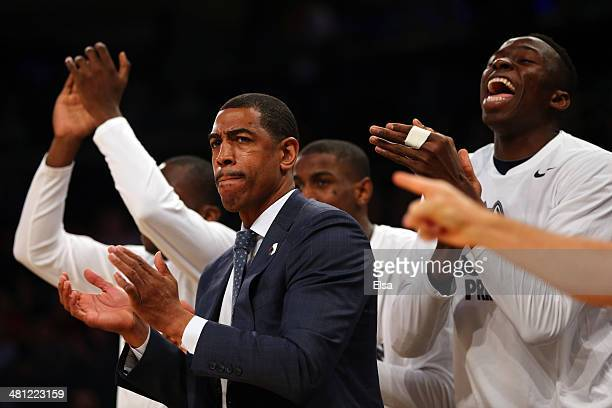 Head coach Kevin Ollie of the Connecticut Huskies claps as his team celebrates behind him as they take on the Iowa State Cyclones during the regional...