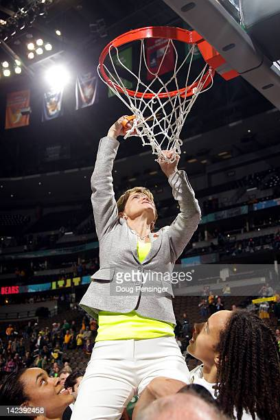 Head coach Kim Mulkey of the Baylor Bears is held up by her players including Brittney Griner as she cuts down a piece of the net in celebration of...