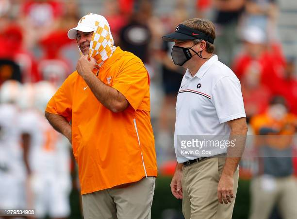 Head coach Kirby Smart of the Georgia Bulldogs and head coach Jeremy Pruitt of the Tennessee Volunteers converse during pregame warmups at Sanford...