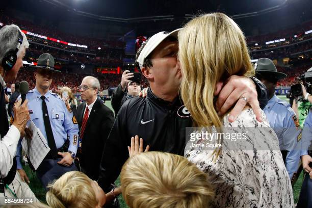 Head coach Kirby Smart of the Georgia Bulldogs celebrates with his wife Mary Beth Lycett after beating the Auburn Tigers in the SEC Championship at...