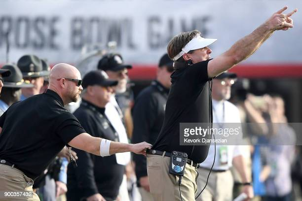 Head Coach Kirby Smart of the Georgia Bulldogs is held back by his belt from the sidelines in the 2018 College Football Playoff Semifinal game...