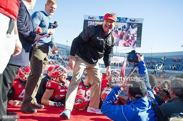 Head coach Kirby Smart of the Georgia Bulldogs laughs after handing the Liberty Bowl Trophy to his players after defeating the TCU Horned Frogs at...