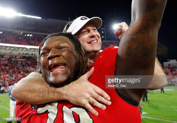 Head coach Kirby Smart of the Georgia Bulldogs leaps on the back of Isaiah Wilson as they celebrate their 1913 win over the Texas AM Aggies at...