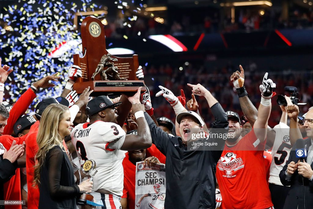 head coach Kirby Smart of the Georgia Bulldogs, Roquan Smith #3 and the team celebrate with the SEC Championship Trophy after beating Auburn Tigers in the SEC Championship at Mercedes-Benz Stadium on December 2, 2017 in Atlanta, Georgia.
