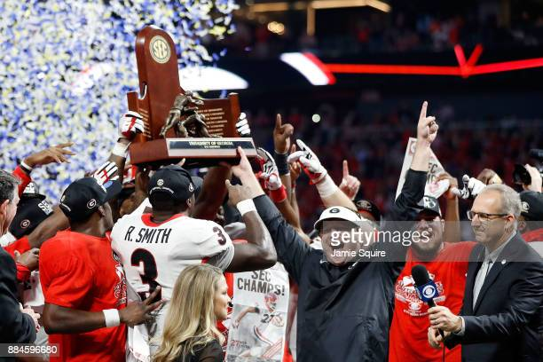 head coach Kirby Smart of the Georgia Bulldogs Roquan Smith and the team celebrate with the SEC Championship Trophy after beating Auburn Tigers in...