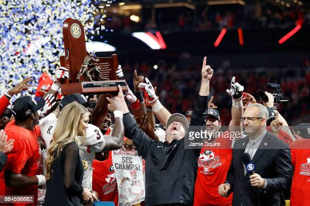 Head coach Kirby Smart of the Georgia Bulldogs, Roquan Smith and the team celebrate with the SEC Championship Trophy after beating Auburn Tigers in...