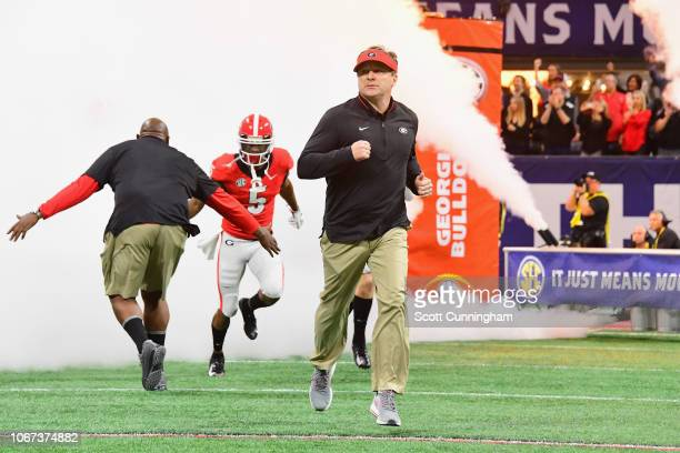 Head coach Kirby Smart of the Georgia Bulldogs runs onto the field before the 2018 SEC Championship Game against the Alabama Crimson Tide at...