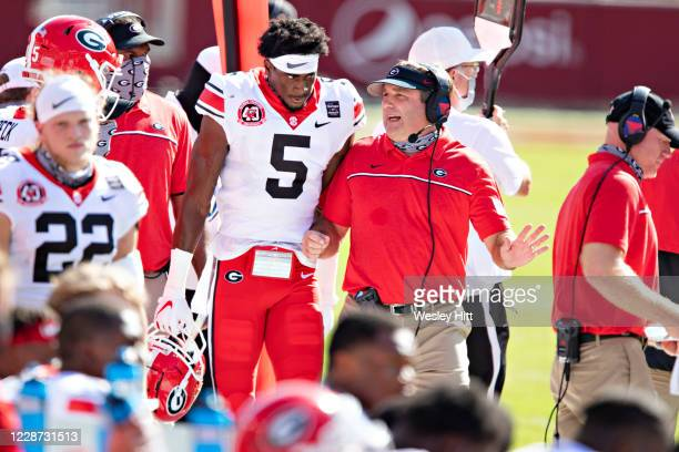Head Coach Kirby Smart talks with Matt Landers of the Georgia Bulldogs on the sidelines in the first half of a game against the Arkansas Razorbacks...