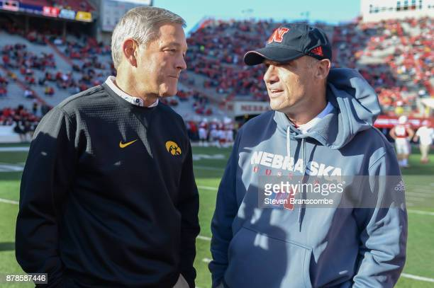 Head coach Kirk Ferentz of the Iowa Hawkeyes and head coach Mike Riley of the Nebraska Cornhuskers meet on the field before the game at Memorial...