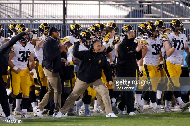Head coach Kirk Ferentz of the Iowa Hawkeyes reacts from the sideline with players and coaches after a fourth down defensive stop against the Penn...