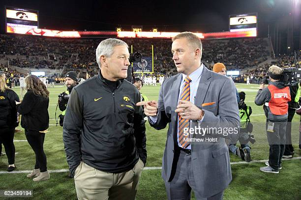 Head coach Kirk Ferentz of the Iowa Hawkeyes talks with television personality Kirk Herbstreit before the matchup against the Michigan Wolverines on...