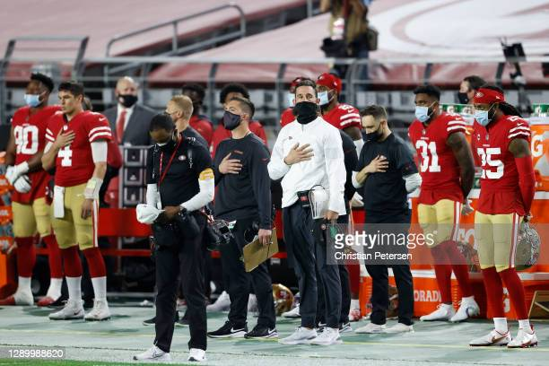 Head coach Kyle Shanahan of the San Francisco 49ers and his team stand during the national anthem prior to a game against the Buffalo Bills at State...