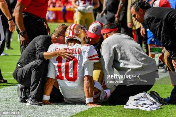 Head coach Kyle Shanahan of the San Francisco 49ers and the team training staff examine quarterback Jimmy Garoppolo on the sideline after being hurt...