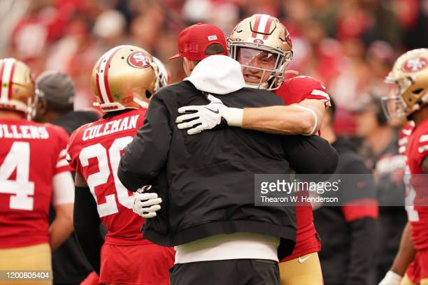 Head coach Kyle Shanahan of the San Francisco 49ers hugs Kyle Juszczyk during warm ups prior to their game against the Green Bay Packers in the NFC...