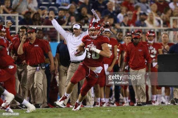 Head coach Lane Kiffin raises his arms as Harrison Bryant of the Florida Atlantic Owls runs with the ball down the sideline against the Middle...