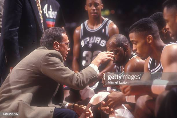 Head coach Larry Brown of the San Antonio Spurs talks to his players during a time out of a basketball game against the Washington Bullets at the...