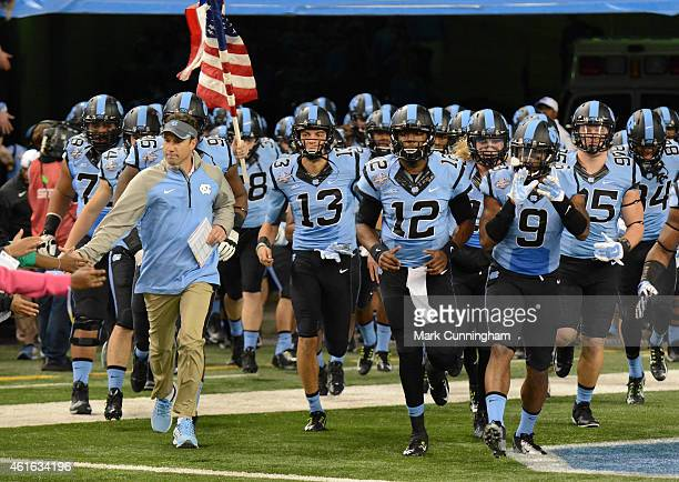 Head coach Larry Fedora Mack Hollins Marquise Williams and Travis Hughes of the North Carolina Tar Heels lead their team onto the field prior to the...